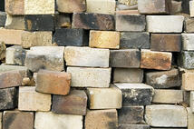 Bricks of various colors and conditions in a stack